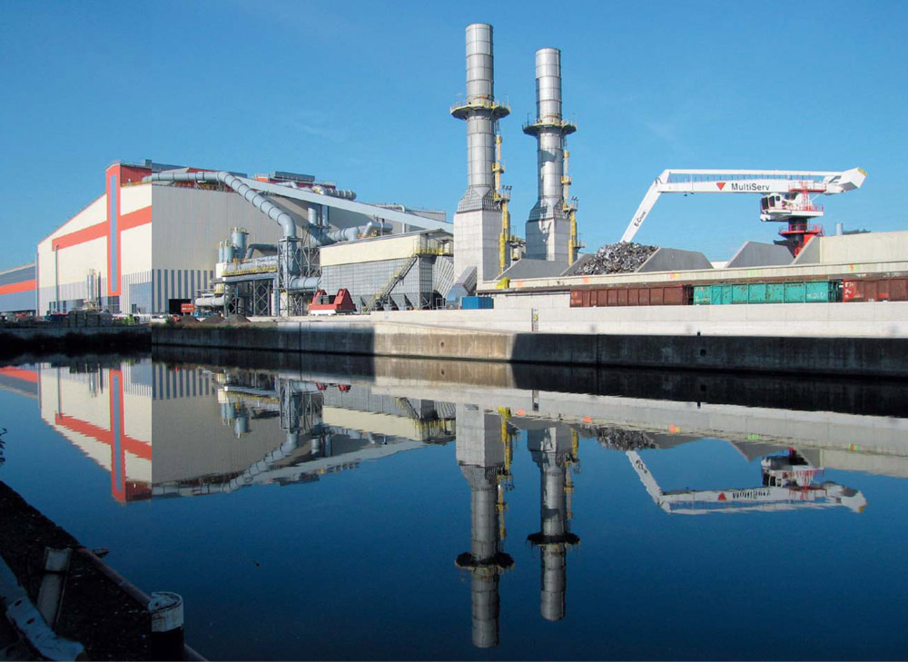 For this milestone project, Siemens VAI was re-sponsible for the overall engineering, erection,and commissioning of the steel works. This included the turnkey supply of a 160-ton electric arc furnace, a 180-ton AOD converter, a twin-180-ton-standladle-treatment station with a common furnace, a single-strand slab caster in addition to auxiliary plants and the dedusting and automation systems. The plant was compactly designed with totally optimized logistics and offers the possibility for future expansion.  Electric arc furnace  Raw materials are transported to the site by either rail or water transport. In the scrap yard different scrap qualities are weighed, loaded in baskets, and then transported to the EAF bay. The EAF itself has an eight-meter diameter, and as such is the largest sized furnace employed in stainless steel making. It is complimented by a 160-MVA transformer which is the most powerful in the world used in stainless steel production. A Level 3 planning system provides the setpoints to the automation system. A process model calculates a cost-optimized melting practice for each single scrap blend.The required flux and alloy additions are accurately calculated and automatically charged to the furnace. Adynamic regulation system maximizes the power in-put and monitors and controls thermal radiation. The economy of operation is further increased through the injection of oxygen and carbon/FeSi through the open slag door by means of a water-cooled lance. This promotes the formation of a foamy slag in the refining phase, which considerably improves the furnace melting efficiency through reduced energy losses. During operations, the EAF is completely enclosed within a dog house to minimize noise and dust emissions.160 tons of liquid stainless steel are tapped into a transfer ladle every 70 minutes on average. Sampling,temperature measurements, and the remaining slag quantity present in the steel is carried out before charging into the AOD.  picture Carinox stainless steelmaking plant  AOD converter  Decarburization of the heat is carried out in an AOD converter. With a diameter of 5.8 meters and a heat size of 180 tons, this is currently the largest converter in the world used in the production of stainless steel. Oxygen and nitrogen or argon are blown into the heat by means of nine under-bath tuyeres installed in the side-walls. Outer annular shroud tuyeres and the application of an intelligent wear-monitoring system protect the inner pipes and maximize their lifetime. The use of a top lance accelerates initial decarburization. The Ugine & ALZ-developed TOP AOD process model allows the exact process targets to be met on the basis of input data from the EAF, raw materials, and additives.The average AOD tap-to-tap time is 70 minutes. During longer waiting times, the temperature of the converter can be maintained using a burner and heat-insula-tion hood which covers the converter opening when the converter is tilted into the horizontal position. The ferro-alloy additive-handling and -charging system is comprised of 28 bins and operates fully auto-matically. It supplies both the EAF and AOD plants. 	  Twin-stand ladle furnace  The heat is transported by crane from the AOD to one of the twin-ladle furnace stands where stirring, compositional and temperature adjustments of the heat can be carried out. The stands also serve as efficient steel buffers in the case of an unexpected production delay. Alloying materials are charged to the ladle furnacefrom a high-level alloy-bin system and each stand is equipped with a multiline wire-injection facility.  picture 160-Ton electric arc furnace Ferro-alloy/additive-handling system 180-Ton AOD converter Twin-station ladle furnace  Dedusting  system Primary emissions from the EAF (1.3 million m3/h) and AOD (1.1 million m3/h) plants are cleaned in a bag-filter station equipped with pulse-jet cleaning. All other plant emissions are filtered in secondary dedusting systems. A clean-gas dust content of less than 5 mg/Nm3 conforms to the latest European regulations. Valuable solid residues can be recycled to the steel making process.  Continuous slab-casting machine  The continuous slab-casting machine is designed to cast more than one million tons of slabs per year at thicknesses from 150 to 250 mm and in widths ranging from 1,000 to 1,650 mm. Two tun dish cars, each equipped with a submerged entry-nozzle-changing device, preheating hoods, and a nozzle preheater, sup-port long casting sequences. A top-feeding dummy-barsystem considerably shortens downtime between two sequences. Featuring the latest mold technology, hy-draulic oscillators, electromagnetic strand stirring,and Smart Segments, the caster is ideally suited to meet all production and quality requirements. Casting speeds of up to 1.4 meters per minute are possible for ferritic and austenitic steel grades. The automation system includes automatic mold-level control, breakout prediction and dynamic cooling models for improved operational safety. A torch-cutting machine cuts the slab to lengths from 5–12 meters. Slab surfaces are ground by one of the four grinding machines. The close proximity of the Carinox plant to the Carlam hot-strip mill and the use of insulation hoods allow the slabs to be hot-charged to the rolling mill.  Leading supplier  With the completion of this project, the Arcelor Mittal group, the largest steel producer in the world today,has acquired a leading position in the stainless steel market. The Ugine & ALZ division in Charleroi, Belgium now supplies approximately 25% of the European market with high-quality stainless steel hot- and cold-rolled products.  Concluding remarks  The large production capacity of the stainless steelworks, coupled with efficient and flexible production scheduling, are key reasons for the economic feasibility of this plant. Advanced process technology, robust and reliable plant equipment, well-trained operational personnel, and the excellent cooperation between the Ugine & ALZ and Siemens VAI project teams were decisive for the overall success of this project.