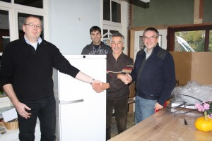"Mr. Robert Acoe, founder of ""Kruiskenshoeve"" was very happy with the new fridge. It was donated by E-Crane. From left to right: Filip Van Cauwenberghe, Bart Matthys, Robert Accoe, Lieven Bauwens."